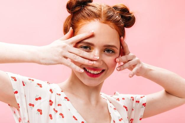 Donna allegra con i capelli rossi esamina la macchina fotografica con il sorriso. ritratto di donna in maglietta bianca su sfondo rosa.