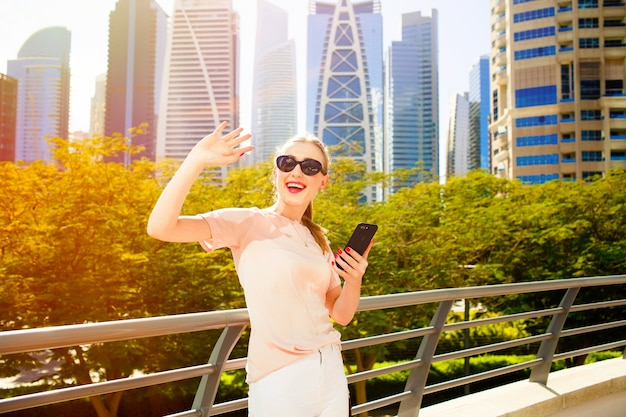 Cheerful woman with red lips raises her hand up while she stands on bridge before skyscrapers