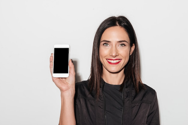 Cheerful woman with red lips showing display of mobile phone.