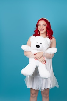 Cheerful woman with red wavy hair in white dress hugs big white teddy bear