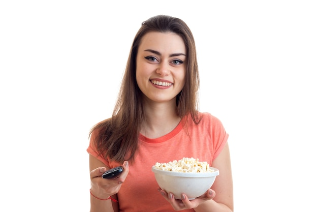 A cheerful woman with remote control from the tv and popcorn smiles isolated on white