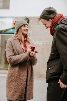Веселая женщина с кольцом, предлагающая мужчине на улице