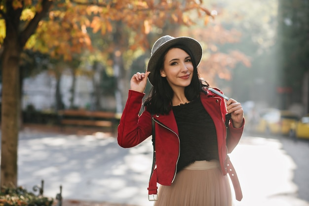 Cheerful woman with short black hair posing in sunny september day