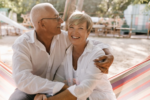Cheerful woman with short blonde hairstyle in white clothes sitting on hammock and hugging with smiling man in eyeglasses on beach.