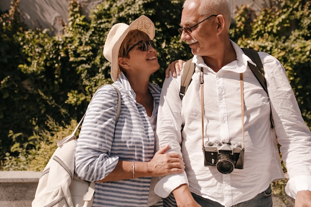 Cheerful woman with short hair and backpack in sunglasses and striped blouse looking at man with mustache in white shirt with camera outdoor.