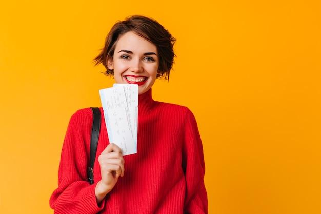 Веселая женщина с короткими волосами держит билеты