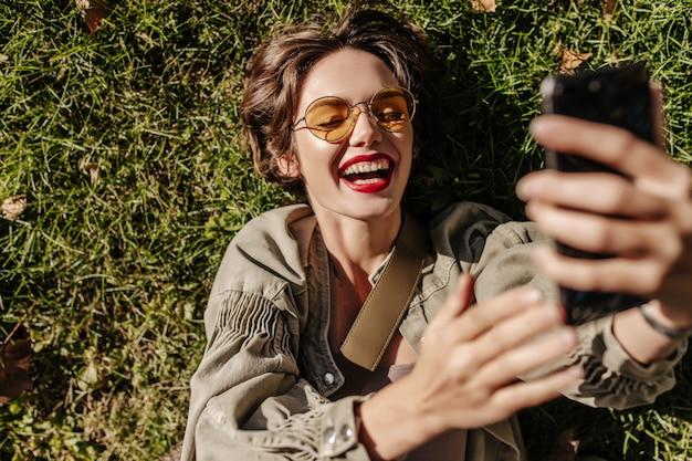 노란색 안경에 짧은 머리를 가진 쾌활 한 여자는 웃음과 외부 잔디에 거짓말. 야외에서 selfie을 만드는 데님 재킷에 여자입니다.