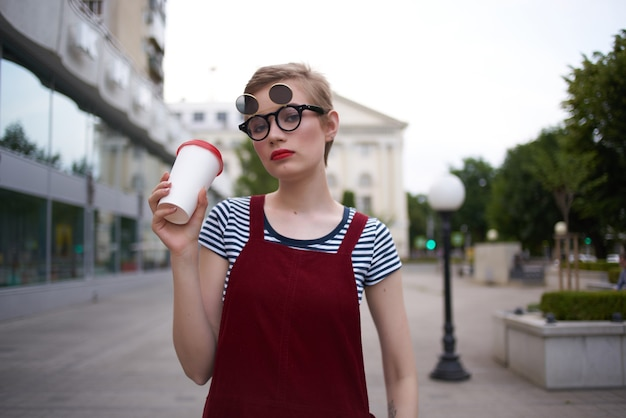 飲み物と短い髪の屋外ガラスの陽気な女性