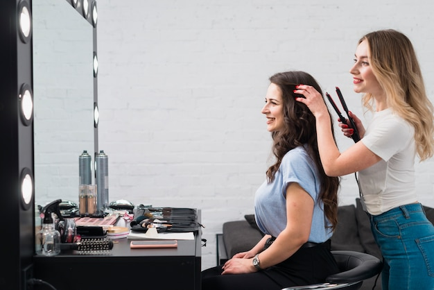 Cheerful woman with stylist doing hairstyle in studio