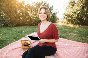 Cheerful woman with tablet on picnic