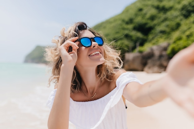 열 대 섬에서 셀카를 만드는 검게 그을린 피부를 가진 쾌활 한 여자. 모래 해변에서 자신의 사진을 찍는 유행 선글라스에 황홀한 젊은 여자의 야외 사진.