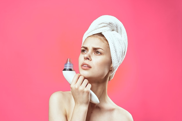 Cheerful woman with a towel on her head vacuum face cleaning pink background