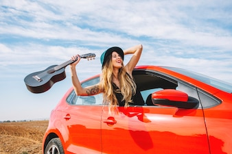 Cheerful woman with ukulele in car