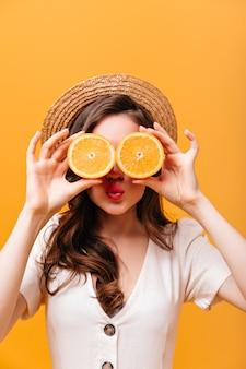 Жизнерадостная женщина с вьющимися волосами прикрывает глаза апельсинами. леди в канотье и рубашке, позирует на изолированном фоне.