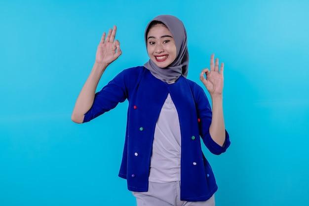 Жизнерадостная женщина в хиджабе показывает знак ок, улыбается, говорит да, поощряет что-то купить, делает хороший жест