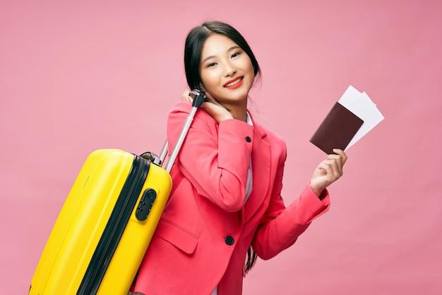 Веселая женщина с желтым чемоданом, паспортом и билетами на самолет в отпуск