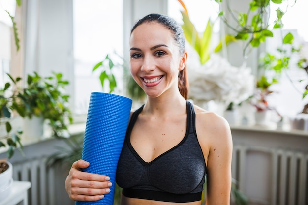 Cheerful woman with yoga mat