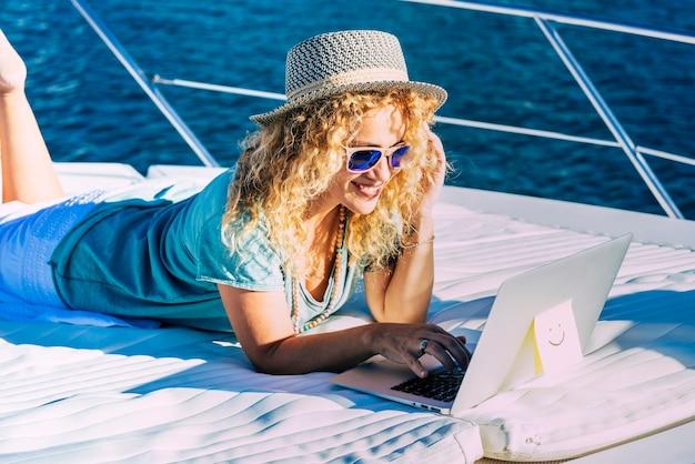 ラップトップコンピューターで屋外で働く陽気な女性は、自由とインターネット接続を楽しんでいるボートに横になります-人々の概念とスマートに働く現代のライフスタイル-新しいジョブオフィスの概念