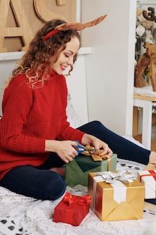 クリスマスプレゼントを包む陽気な女性