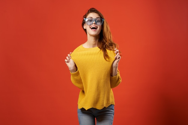 쾌활 한 여자 노란색 스웨터 안경 패션 옷 스튜디오 빨간색 배경. 고품질 사진