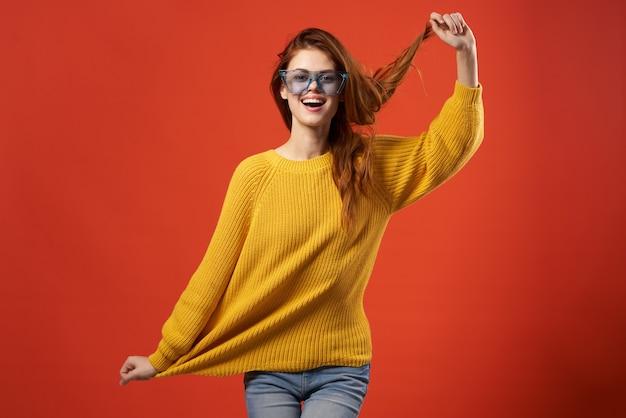 쾌활한 여자 노란색 스웨터 안경 패션 옷 스튜디오 빨간색 배경