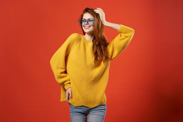 쾌활 한 여자 노란색 스웨터 안경 패션 옷 스튜디오 빨간색 배경