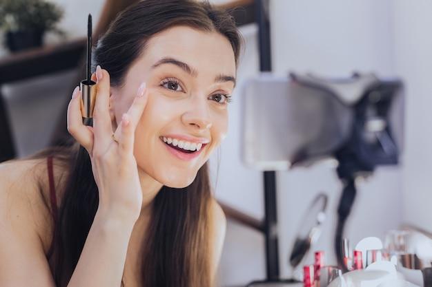 陽気な女性。新しい化粧品についてのブログを撮影しながら広く笑っている若い陽気な女性