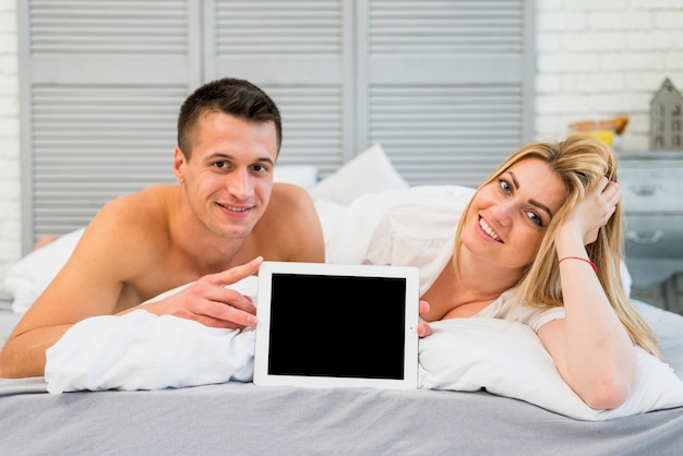 Cheerful woman and young smiling man showing photo frame in bed