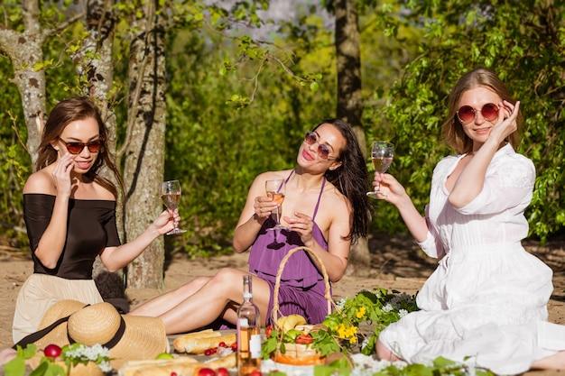 陽気な女性はワインで自然の中で休んでいます