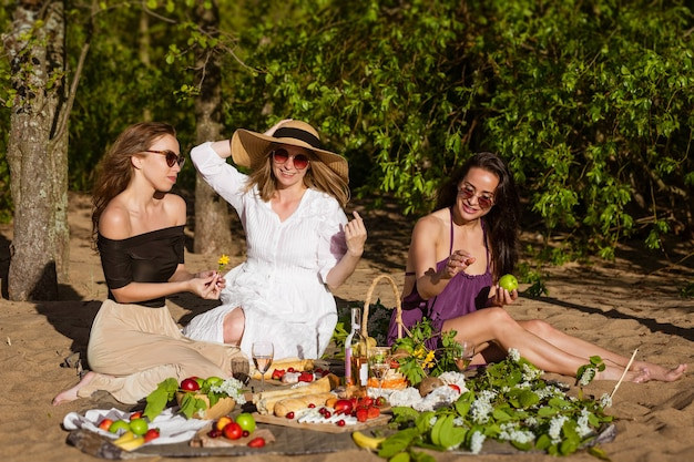 Cheerful women are resting in nature with wine