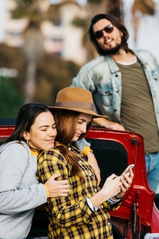 Cheerful women embracing lady with smartphone near car trunk and man leaning out from automobile