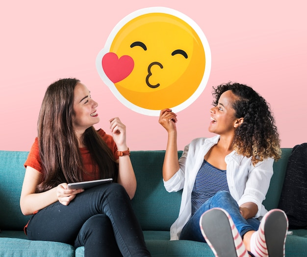 Cheerful women holding a kissing emoticon icon