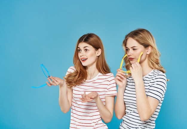 陽気な女性はファッションの夏のスタイルのライフスタイルの青い背景を抱擁します