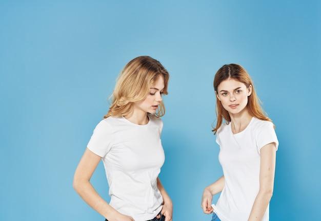 青い壁に白いtシャツを着た陽気な女性