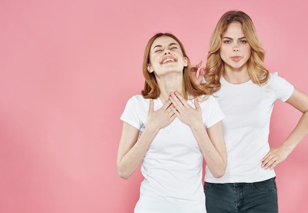 白いtシャツを着た陽気な女性は、社交的なライフスタイルの魅力的なピンクの背景を抱擁します