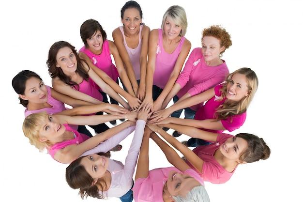 陽気な女性たちが円に入り、乳がんのためにピンクのカメラを見上げた