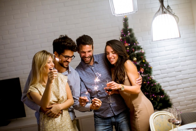 Cheerful women and men celebrating new year eve with sparkles and wine at home