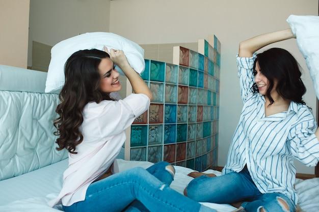 Donne allegre che giocano con i cuscini sul letto