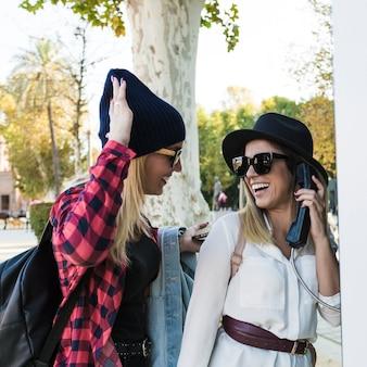 Веселые женщины говорят по телефону на улице