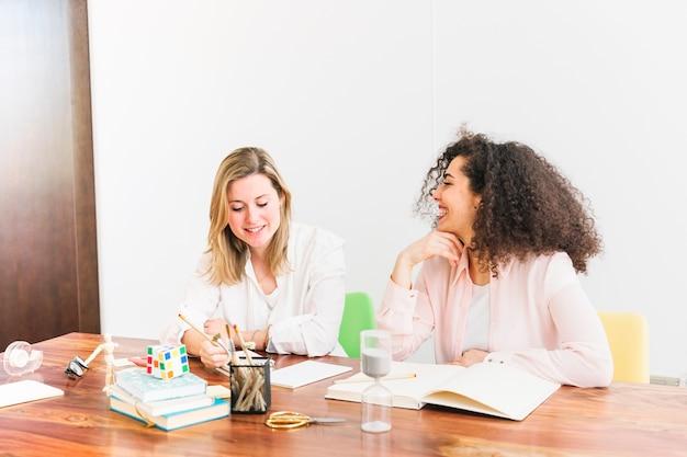 Веселые женщины, обучающиеся за столом