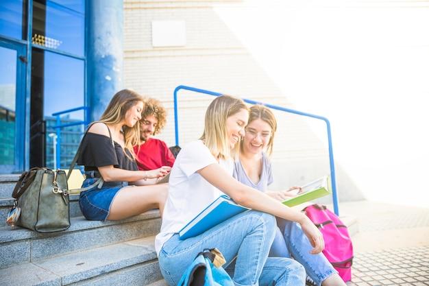 友人の近くの大学の階段で勉強している陽気な女性