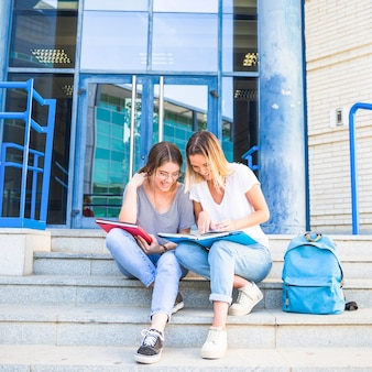 Cheerful women studying on university steps