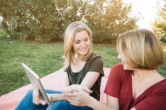 Cheerful women using tablet on picnic