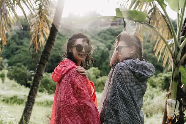 비옷에 숲 주위를 산책하는 쾌활 한 여자. 정글에 서있는 선글라스에 행복 한 여자 친구의 야외 촬영.