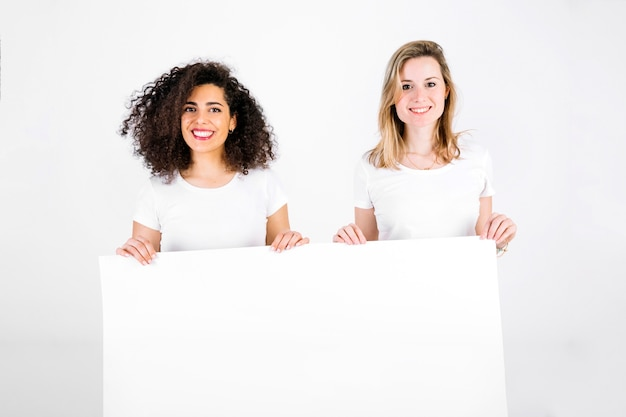 Cheerful women with blank poster
