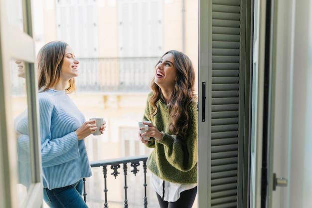 Веселые женщины с кружками на балконе