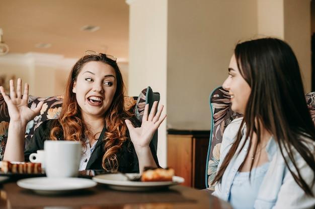 Веселые женщины с рыжими волосами рассказывают историю своей подруге, сидя в кафе.