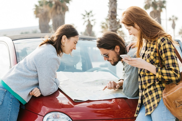 Cheerful women with smartphone near man looking at map on car hood