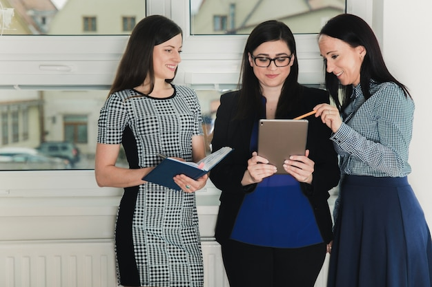 Cheerful women with tablet in office