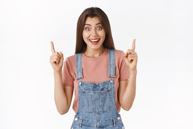 陽気な、不思議な興奮した魅力的な女の子が大きなニュースを共有し、上げられた指を上に向け、トッププロモーションを表示し、面白がって笑って、クールなイベントに参加したい、ブラックフライデーを待つことができない、白い背景